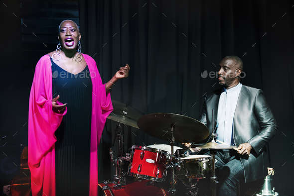 Drummer and singer performing in an event - Stock Photo - Images