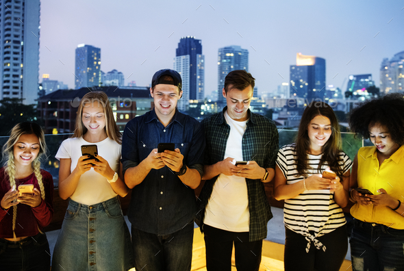 Happy group of young adults using smartphones in the cityscape - Stock Photo - Images
