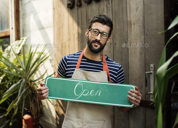 "A person holding an ""open"" sign - Stock Photo - Images"