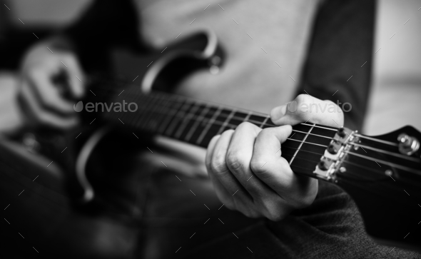 Teenage boy playing an electric guitar in a bedroom hobby and music concept - Stock Photo - Images
