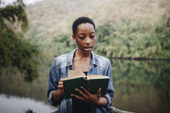 African American woman alone in nature reading a book leisure concept - Stock Photo - Images
