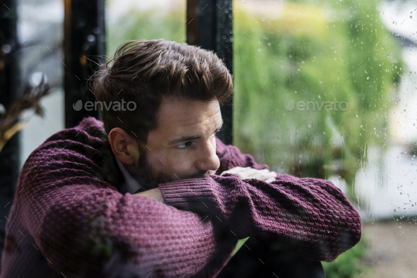 Thoughtful man looking out the window - Stock Photo - Images