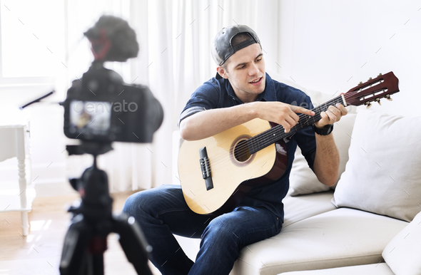 Male vlogger recording music related broadcast at home - Stock Photo - Images