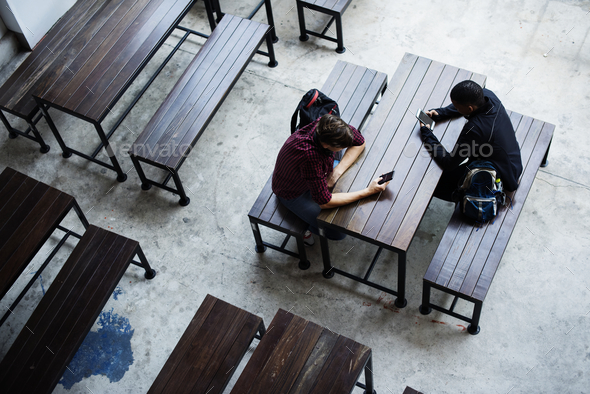 Teenage boys sitting together in a empty canteen - Stock Photo - Images
