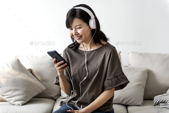 Asian woman enjoying music at home - Stock Photo - Images