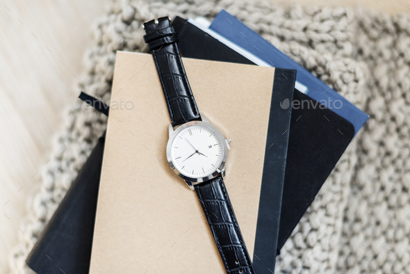 Closeup of watch on notepads - Stock Photo - Images