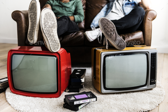 Two man sitting and two retro television - Stock Photo - Images