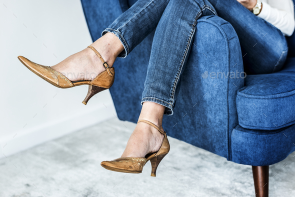 Closeup pair of feminie legs on the sofa wearing heels - Stock Photo - Images