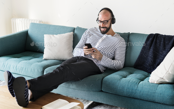 Man using device on couch - Stock Photo - Images
