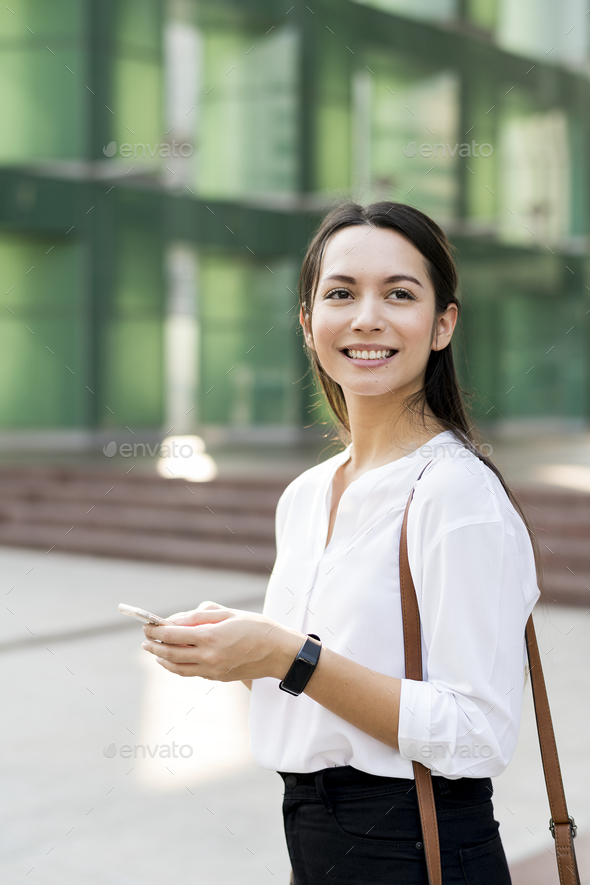Asian woman smiling and playing on phone - Stock Photo - Images