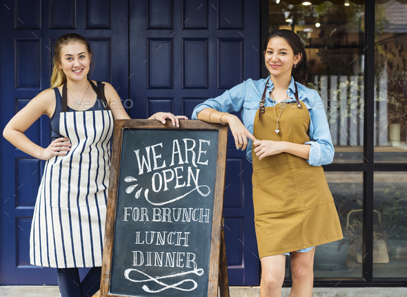 Cheerful business owners standing with open blackboard - Stock Photo - Images