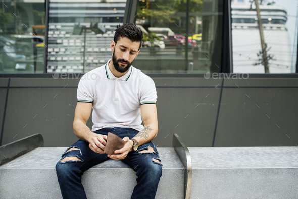 Man sitting checking his money - Stock Photo - Images