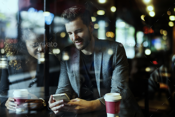 Casual man using mobile phone in the cafe - Stock Photo - Images