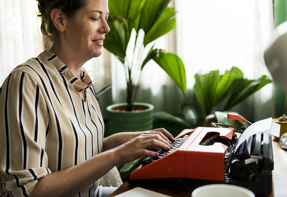 Woman typing on a retro typewriter - Stock Photo - Images