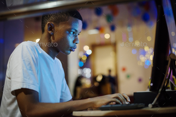 African american boy using a computer at night - Stock Photo - Images