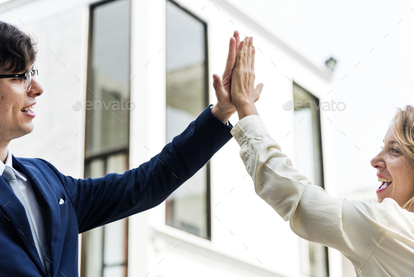 Businesspeople giving a high five together - Stock Photo - Images