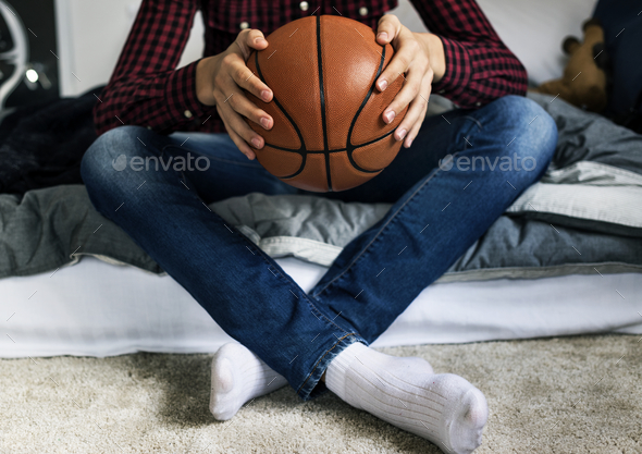 Teenage boy in a bedroom holding a basketball hobby aspiration and loneliness concept - Stock Photo - Images