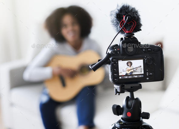 Female vlogger recording music related broadcast at home - Stock Photo - Images