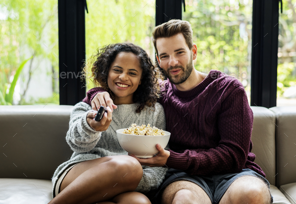 Couple watching TV having popcoprn - Stock Photo - Images