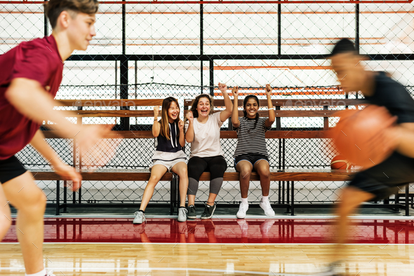Teenage girls cheering the boys playing basketball - Stock Photo - Images
