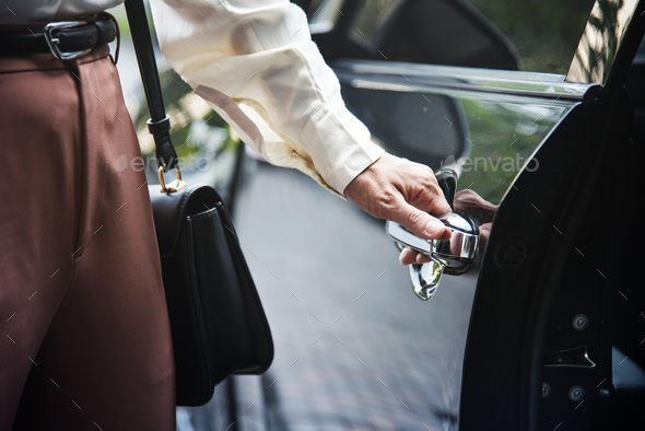 Woman getting into a car - Stock Photo - Images