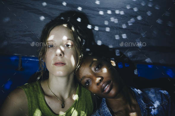 Friends sitting together in a tent - Stock Photo - Images