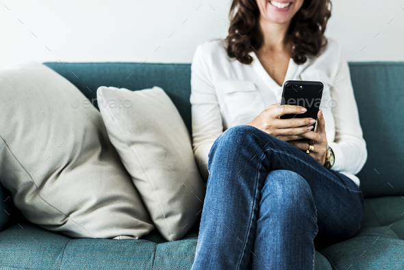 Woman using mobile phone on the sofa - Stock Photo - Images