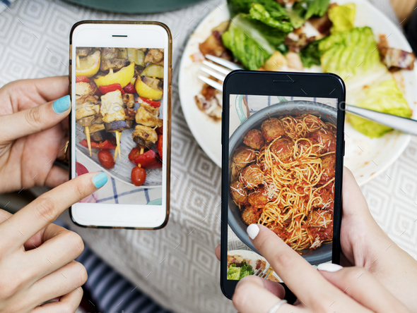 People sharing food photos on mobile phone - Stock Photo - Images
