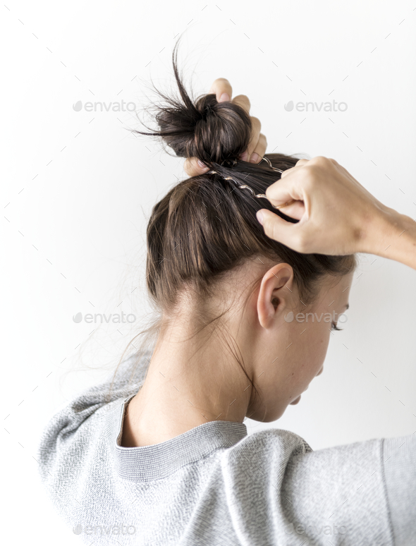 Woman making hair bun - Stock Photo - Images