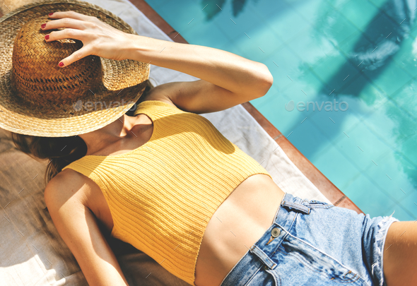 Young woman tanning poolside - Stock Photo - Images
