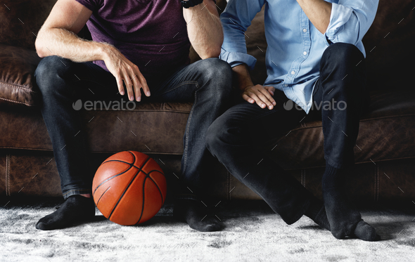 Man sitting together on a couch watching sport - Stock Photo - Images