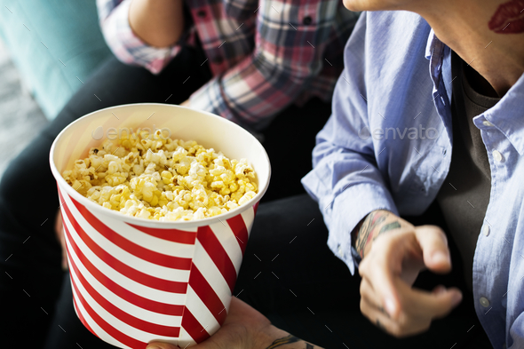 Friends enjoying a movie on friday night - Stock Photo - Images