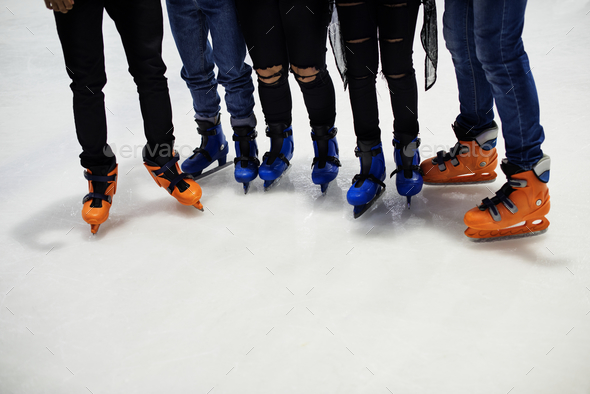Feet closeup of group of friends ice skating together - Stock Photo - Images