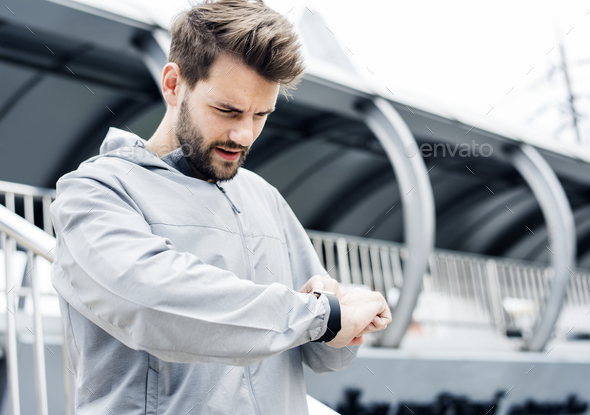 Sporty man looking at his smartwatch - Stock Photo - Images
