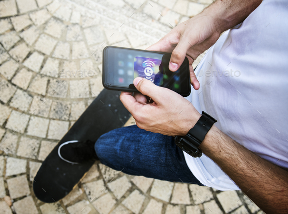 Young adult man using a smartphone music application outdoors - Stock Photo - Images