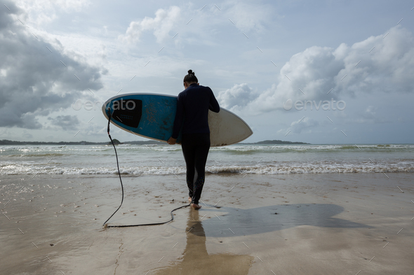 Woman going to surf in the ocean - Stock Photo - Images