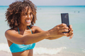 Cheerful ethnic woman taking selfie on beach - PhotoDune Item for Sale