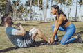 Woman helping man with exercise in park - PhotoDune Item for Sale