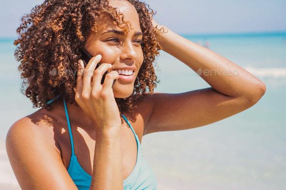 Laughing woman talking phone at seaside - Stock Photo - Images