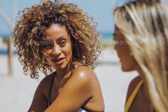 Beautiful women chatting on beach - Stock Photo - Images