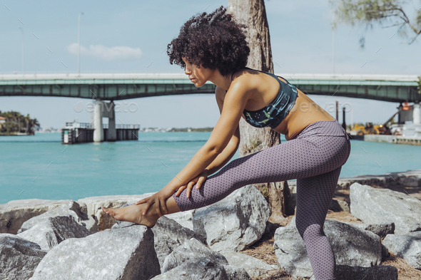 Black girl working out on riverbank - Stock Photo - Images