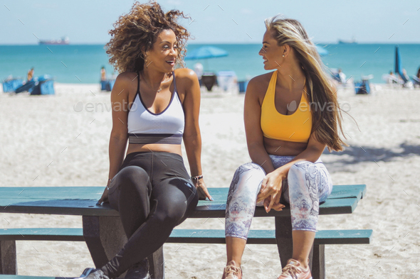 Lounging girlfriends in sportswear on beach - Stock Photo - Images