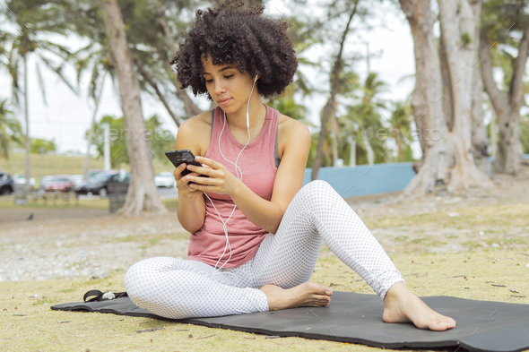 Chilling black girl using phone on mat - Stock Photo - Images