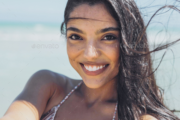 Charming ethnic woman on windy beach - Stock Photo - Images