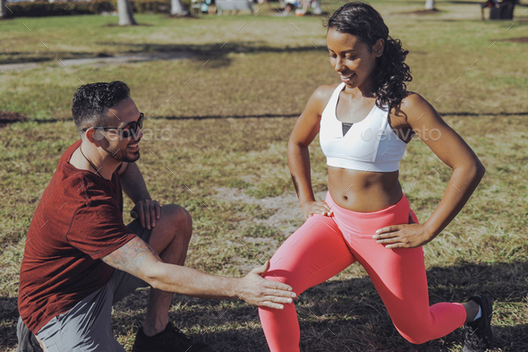 Man helping woman with exercise in park - Stock Photo - Images