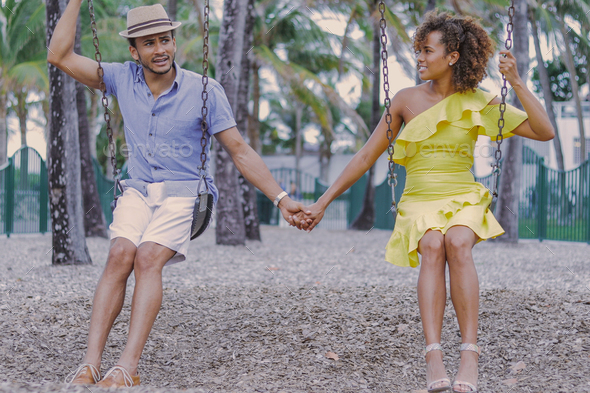 Couple holding hands on swing - Stock Photo - Images
