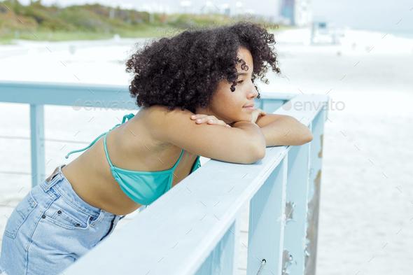 Pretty black girl enjoying view on beach - Stock Photo - Images