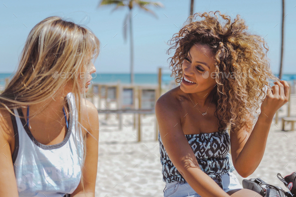 Cheerful women chatting on beach - Stock Photo - Images