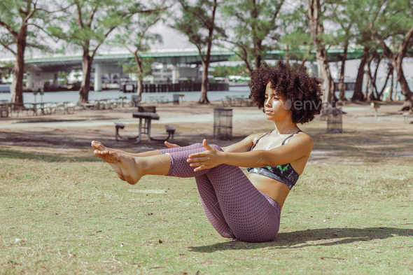 Girl practicing abdomen muscles on meadow - Stock Photo - Images