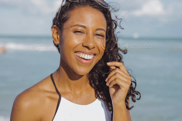 Laughing black woman in swimsuit on beach - Stock Photo - Images